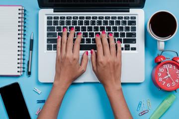 Woman hands typing on keyboard on blue desk.