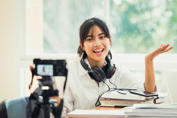 Happy Asian woman videoblog / blogger vlogger recording online course or tutorial coach presentation pass video for teaching live homework sharing online channel social media by mirrorless camera