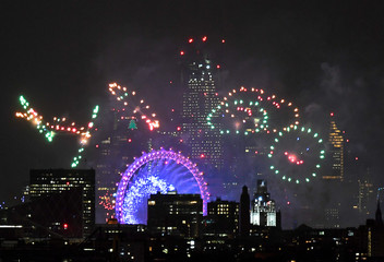 Fireworks light up the sky around the London Eye wheel to welcome the New Year in London, Britain