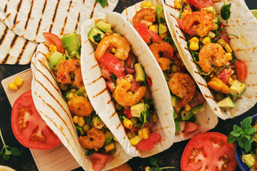 Traditional Mexican food tacos with shrimps and vegetables on a dark background. Top view.
