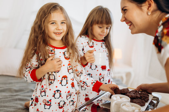 Young mother is bringing cocoa with Marshmallows and cookies to her daughters in pajamas sitting on the bed in the full of light cozy room