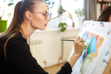 Young beautiful girl in glasses dressed in black blouse sits at the easel and paints a picture in the drawing school