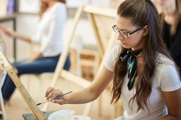 Young brown-haired girl in glasses dressed in white t-shirt and jeans with a scarf around her neck paints a picture in the art studio