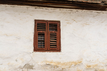 Red window on old traditional Transylvanian log house close up shot.