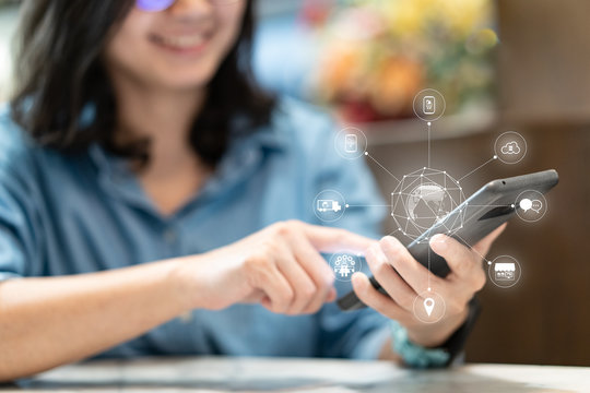Attractive smart asian smile creative freelance woman use her smartphone to shopping in ecommerce website on omni channel platform. She can do every steps on only one mobile.
