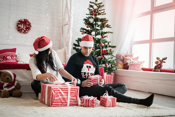 Couple with gift boxes sitting on the floor