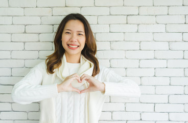 close up woman make heart shape gesture for world kindness day or valentine day or healthy lifestyle concept