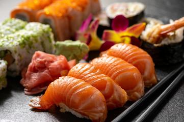 Mix sushi set, on black stone background.
