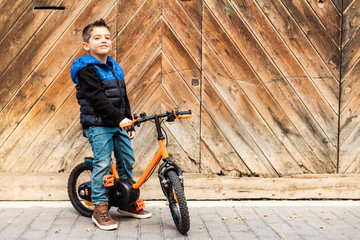 Litle boy with a bike on a wooden door background