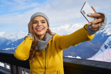 Young woman taking a selfie in winter holiday in mountain.Young woman taking a selfie in winter holiday in mountain.