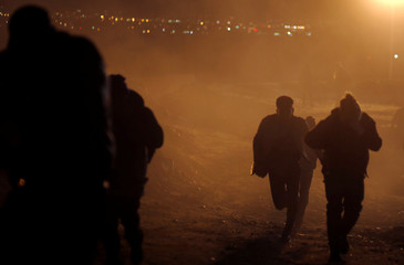Migrants run after U.S. CBP throw tear gas to the Mexican side of the fence as they prepared to cross it illegally, in Tijuana