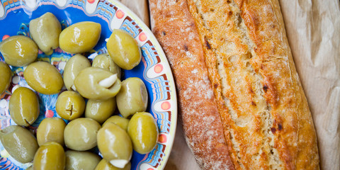 Traditional Mediterranean pickled big Green olives antipasto stuffed with garlic cloves served with fresh soured baguette bread in the background.