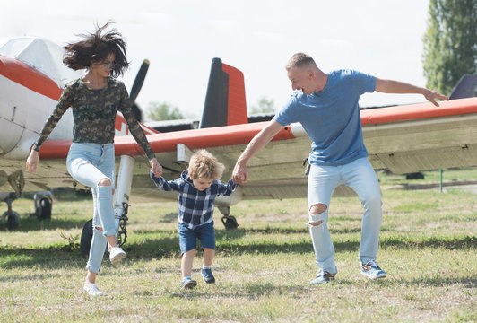 Lets start our journey. Travelling by air. Family on vacation trip. Couple with boy child at plane. Aircraft tour and travel. Air travel. Enjoying travelling fun. Happy family vacation