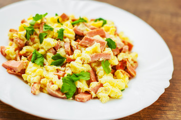 scrambled eggs with ham and cheese in white plate on wooden table background