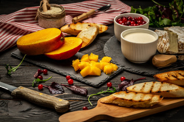 Ingredients for sandwiches with ricotta, mango, cranberry on a dark wooden background, Flat top view. copy space