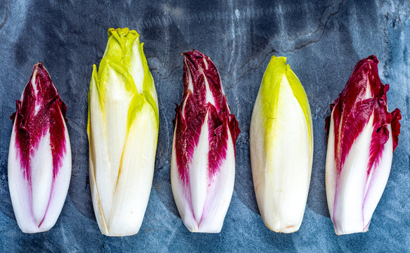Food background, flat lay concept with fresh green Belgian endive or chicory and red Radicchio vegetables, also known as witlof