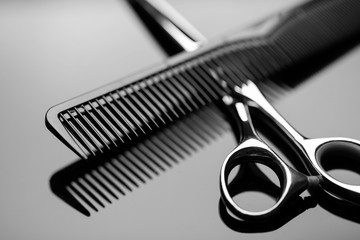 Barber scissors and a hairbrush closeup on the mirror surface of the table. Barber scissors close up.