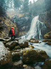 Adventurous man with red jacket and backpack standing on a stone and enjoying the beautiful view of Golling waterfall near Salzburg in Austria at winter. Long exposure view
