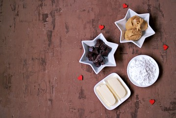 Ingredients for making homemade candies Buckeyes: peanut butter, bitter chocolate, powdered sugar, butter. Copy space, top view.