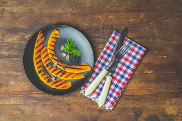 Grilled sliced pumpkin in black ceramic plate on wooden surface