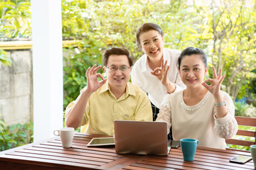 Group Asian elderly men and women are living the tablet and laptop happily with a smile of friendship. By searching for health care information tourism And investment after retirement. Elderly concept