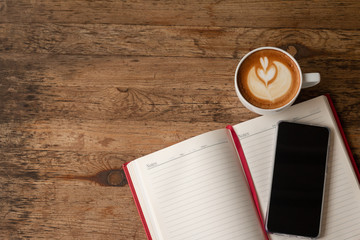 Top view Note book with pencil, smart-phone and a cup of coffee on wood table for Business background