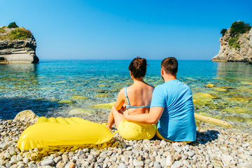 couple sitting on rocky beach looking at sea