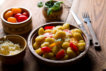 Delicious Italian gnocchi with tomatoes and cheese on wood.