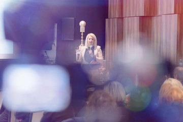 Beautiful business blonde woman with microphone in her hand speaking at the conference or seminar.