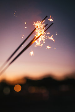 A closeup of fireworks and sparklers during an evening sunset