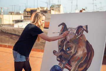 Young woman paint artist drawing at home roof. Picture of bulldog on big canvas. Outdoors art