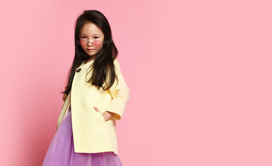Little asian girl in yellow fashion jacket purple dress and modern red sunglasses posing Wall mural