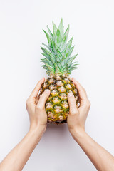 Ripe pineapple woman's in hand isolated on white background.