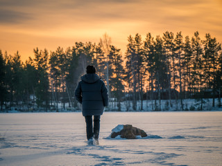 Back of person walking on frozen lake on the ice. Cold weather hike in winter.