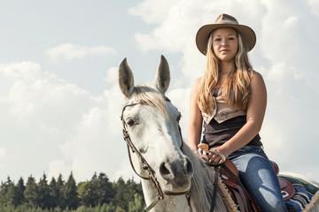 Junge Frau mit Cowboyhut  reitet auf Araberstute