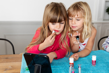Two little girls putting on lipstick together