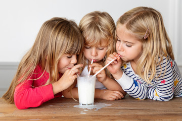 Three girls blowing bubbles in a glass of milk with drinking straws