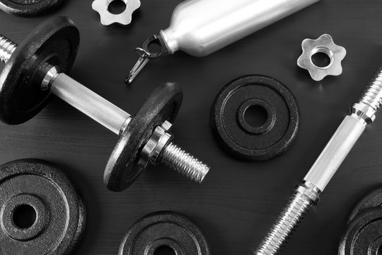 Flat lay composition with dumbbell and parts on dark wooden background