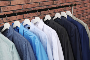 Wardrobe rack with stylish clothes near brick wall