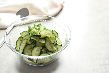 Delicious cucumber salad with dill in bowl on table. Space for text