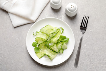 Plate with delicious cucumber salad served on grey table, top view