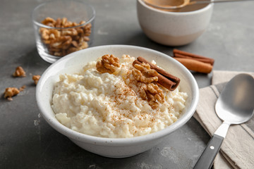 Creamy rice pudding with cinnamon and walnuts in bowl served on grey table