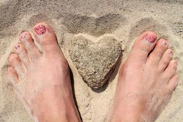 Ein Herz aus Sand halten