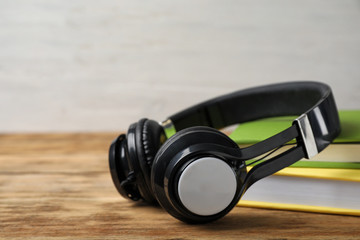 Modern headphones with hardcover books on wooden table, closeup. Space for text