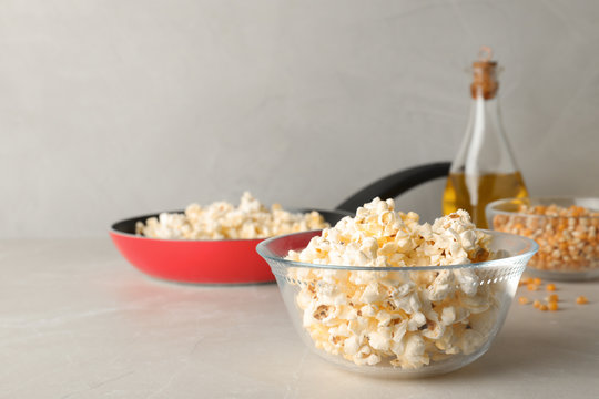 Glass bowl with tasty popcorn on grey table. Space for text