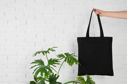 Woman holding eco bag near green plant and brick wall. Mock up for design