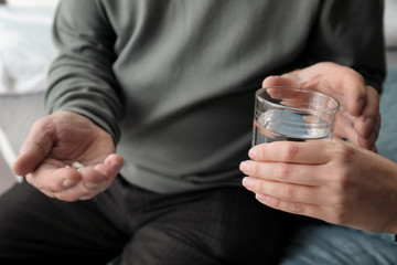 Young woman giving water to senior man with pills, closeup