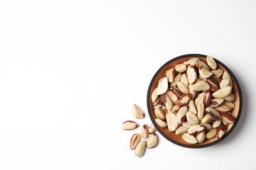 Wooden bowl with Brazil nuts and space for text on white background, top view
