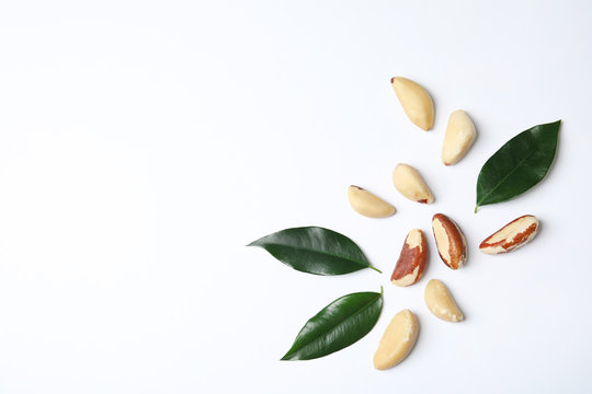 Composition with Brazil nuts and space for text on white background, top view