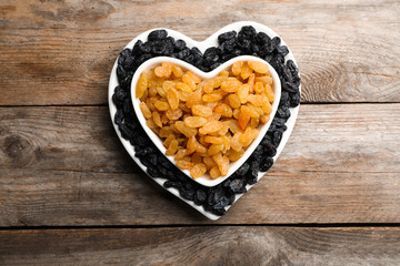 Flat lay composition with raisins on wooden background. Dried fruit as healthy snack
